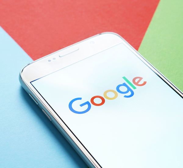 Smartphone showing Google logo on a coloured background