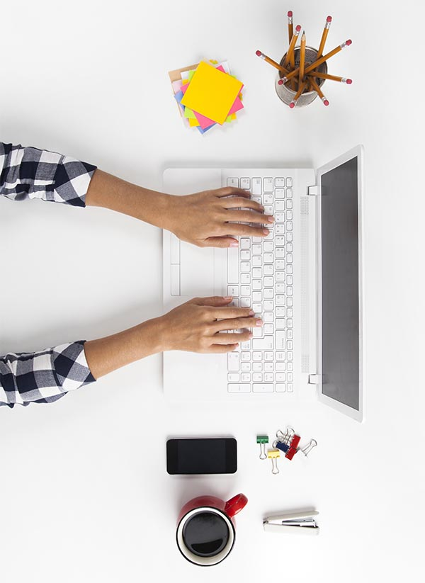 Overhead view of a person working on a white laptop with their fingers on the keys