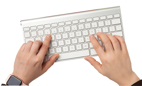 Overhead view of a person's fingers on an iMac keyboard