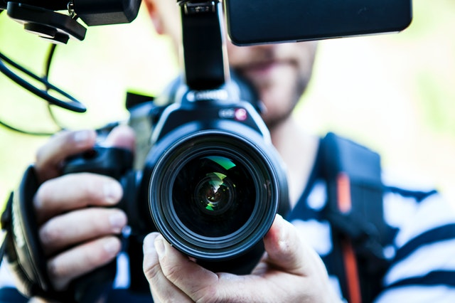 Close up of man with video camera. You are looking straight into the lens.